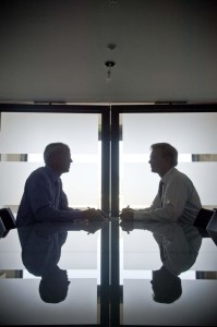 Two businessmen discussing in conference room, side view